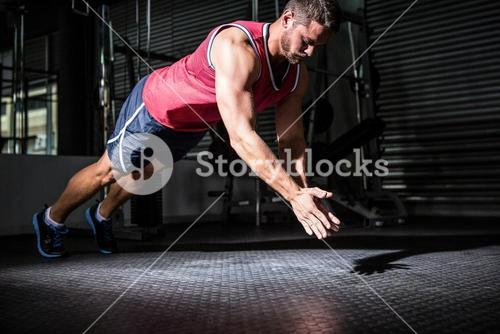 Muscular man doing push-ups with hand clapping