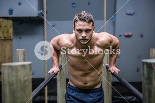 Portrait of muscular man exercising on parallel bars