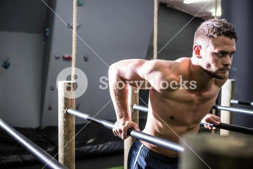 Muscular man exercising on parallel bars