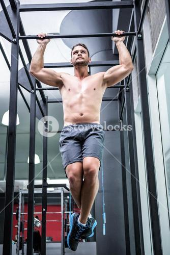 Muscular man doing pull ups