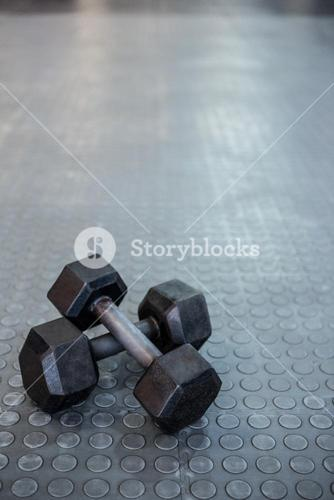 Two dumbbells lying on top of each other on the floor