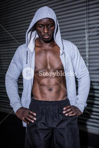 Young Bodybuilder in a hoodie looking worriedly to the ground