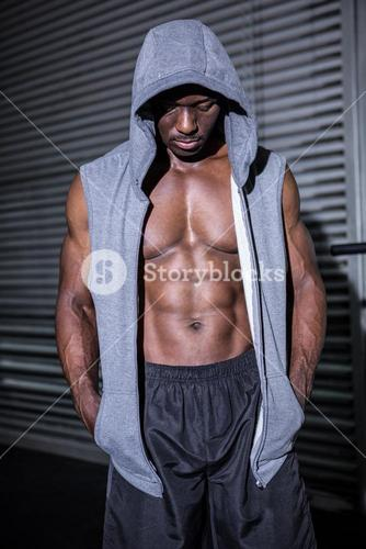 Young Bodybuilder in a hoodie looking at the ground