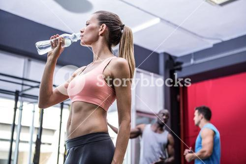 Young woman drinking water from a bottle with colleagues behind her