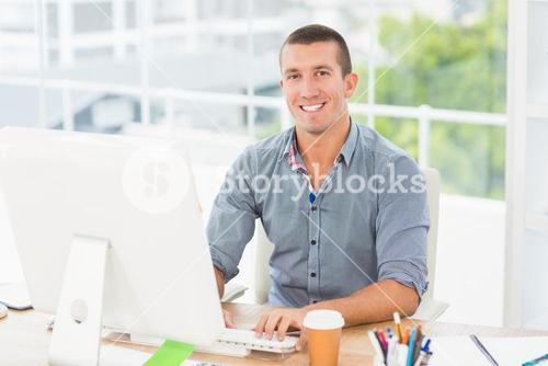 Handsome smiling businessman typing on a computer