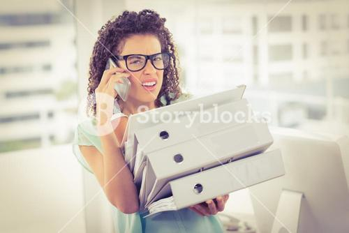Stunned businesswoman carrying a stack of folders