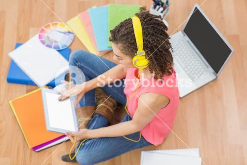 Young creative businesswoman scrolling on tablet