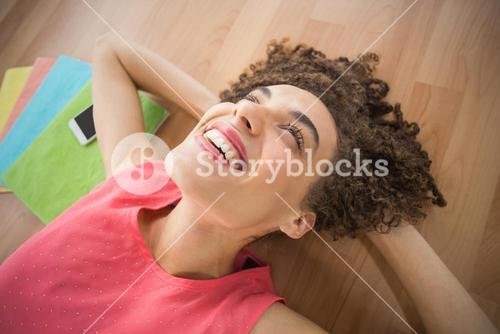 Young creative businesswoman lying on the ground