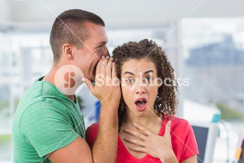 Casual businessman whispering secret to his colleague