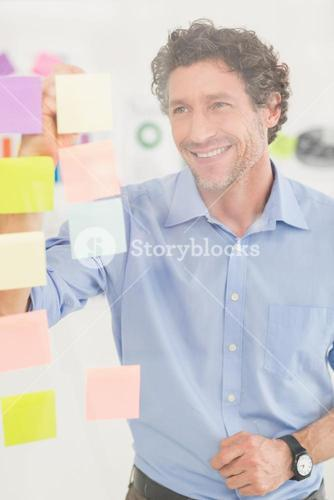 Puzzled businessman looking post its on the wall