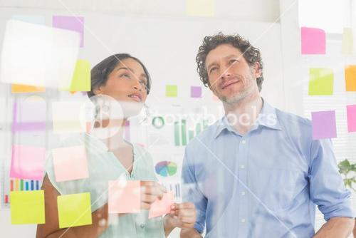 Puzzled business team looking post its on the wall