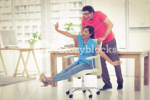 Smiling partners playing together with swivel chair