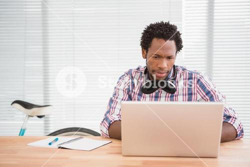 Young businessman looks confused at his laptop