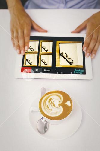Composite image of close-up of digital tablet and coffee on table