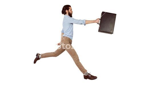 Handsome hipster leaping with briefcase