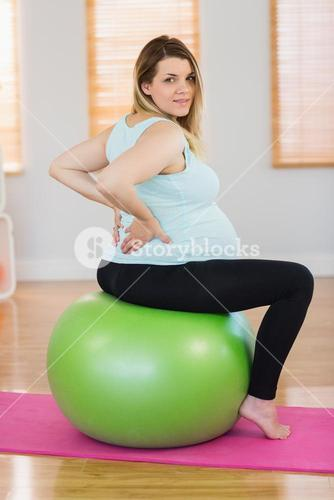Portrait of pregnant woman sitting on exercise ball