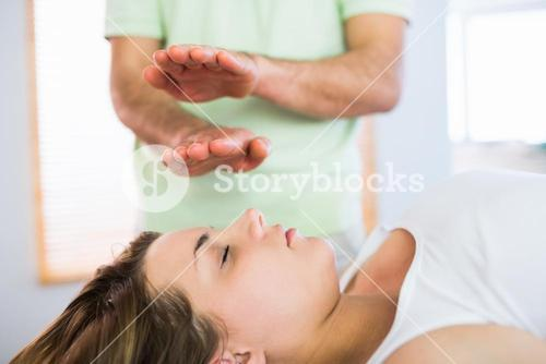 Relaxed pregnant woman getting reiki treatment
