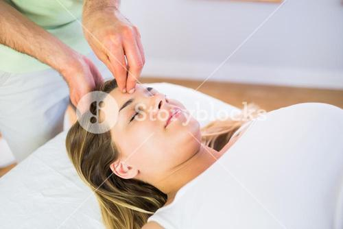 Relaxed pregnant woman enjoying head massage