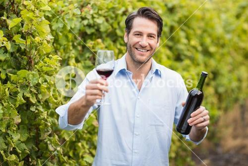 Young happy man smiling at camera and holding a glass of wine