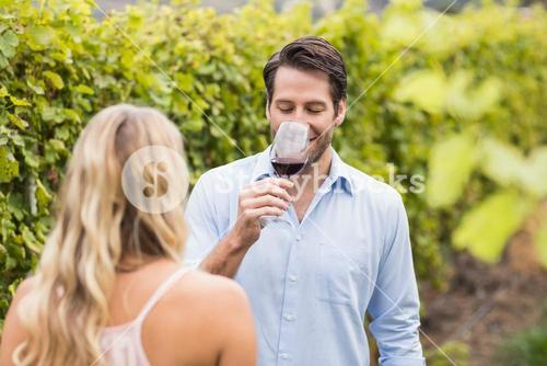 Young happy couple tasting wine