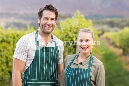 Two young happy vintners looking at camera