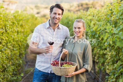 Two young happy vintners holding a basket of grapes and a glass of wine