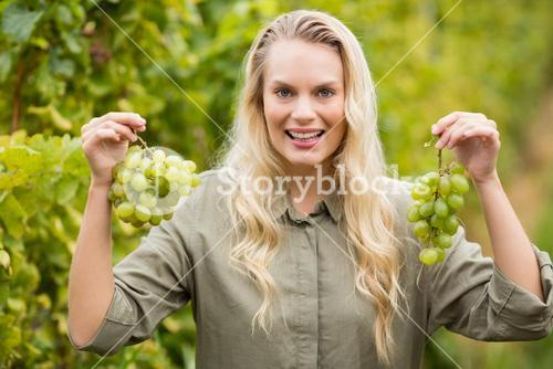 Smiling blonde winegrower holding grapes