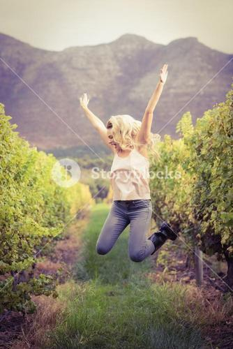 Blonde winegrower jumping in a vineyard