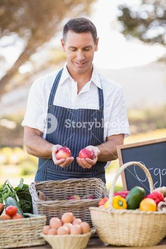Smiling farmer holding two red apples