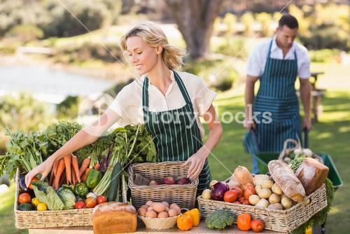 Farmer woman tidying up a table of local food