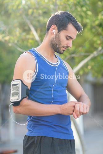 An handsome athlete looking at his pulse