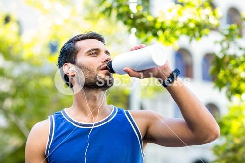An handsome athlete drinking water