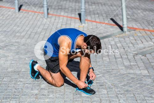 An handsome athlete doing his shoelaces