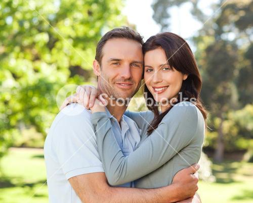 Radiant couple hugging in the park