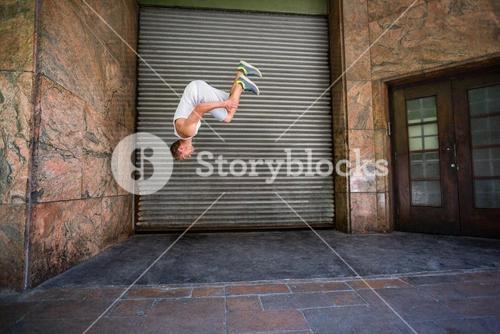 Extreme athlete doing a front flip in front of a building