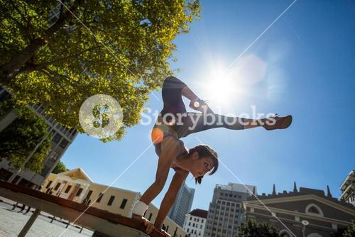 Athletic woman performing handstand on bench