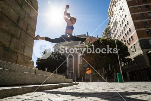 Athletic woman jumping off the stairs and doing split in the air