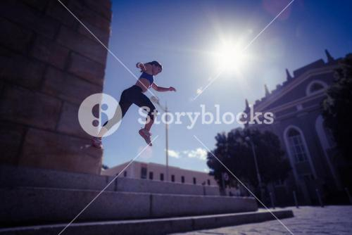 Athletic woman jumping off the stairs