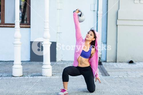 Athletic woman exercising turkish get up with kettlebell