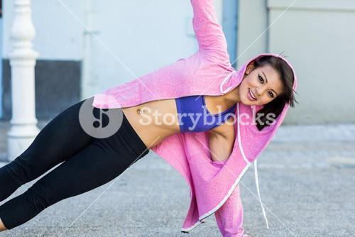 Portrait of athletic woman exercising side plank
