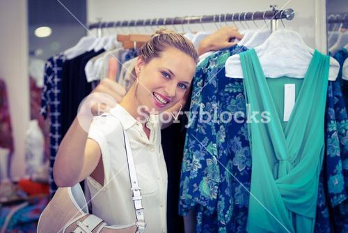Smiling woman browsing clothes and thumbs up