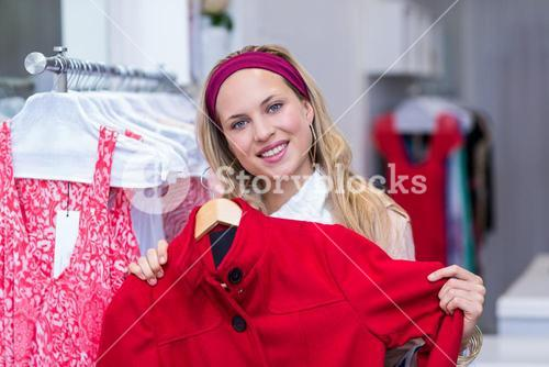 Smiling woman holding red coat