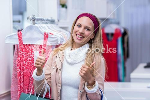 Smiling woman with shopping bags looking at camera with thumbs up