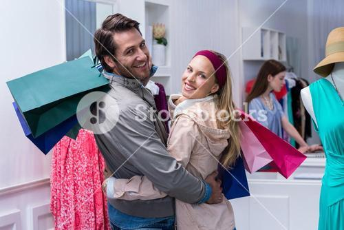 Smiling couple with shopping bags embracing