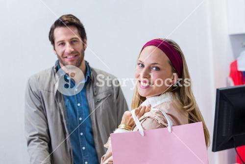 Smiling woman with shopping bag in front of cashier