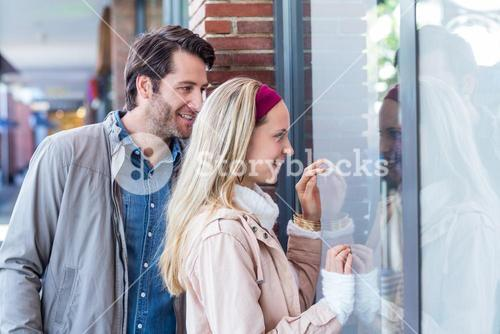 Smiling couple going window shopping