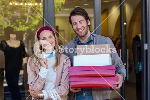 Smiling couple showing credit card and carrying boxes