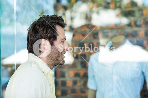 Smiling man going window shopping