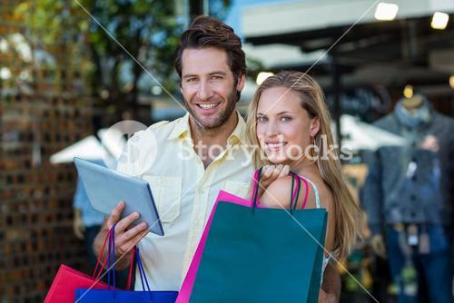 Smiling couple with shopping bags holding tablet computer
