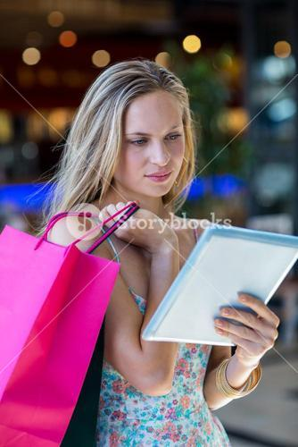 Woman with shopping bags using tablet computer